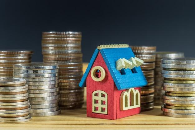 Mini-huis op stapel munten. geld besparen voor vastgoedconcept. Premium Foto