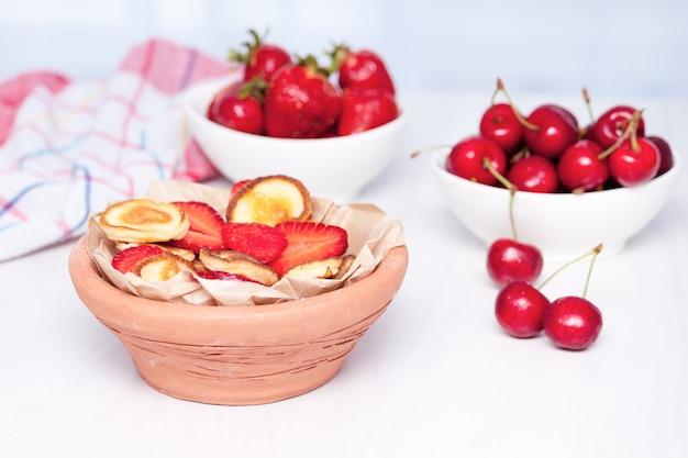 Mini kleine pannenkoeken met aardbeien en kersen op witte houten achtergrond. trendy voedselconcept. Premium Foto