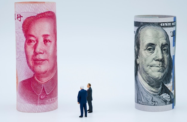 Miniatuur bedrijfsmannen met amerikaanse dollar en china yuan-bankbiljet Premium Foto