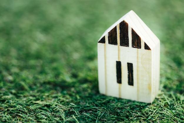 Miniatuur houten witte huis op groen gras. onroerend goed investeringen en huis hypotheek financieel onroerend goed concept. Premium Foto