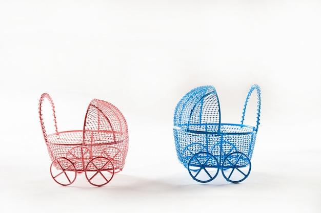 Miniatuur kinderwagens op een wit close-up als achtergrond. baby en zwangerschap concept en kopie ruimte. Premium Foto