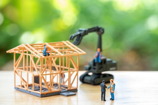 Miniatuur mensen bouwvakker reparatie een model huis model Premium Foto