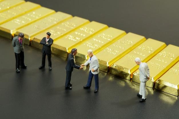 Miniatuur mensen die hand met stapel van goudstaaf schudden op zwarte achtergrond Premium Foto