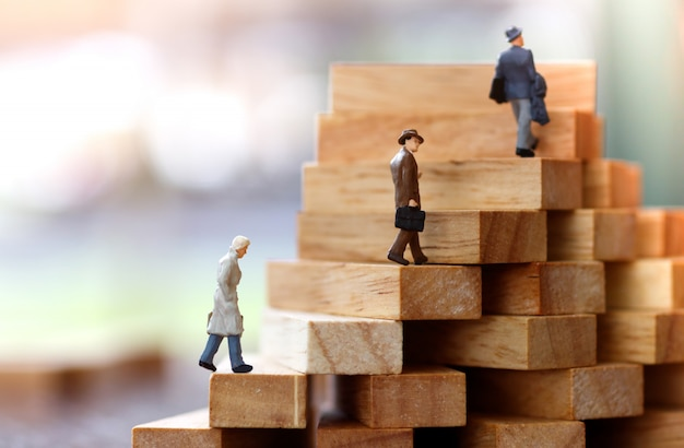 Miniatuur mensen die op stap van houtsnedestapel lopen. Premium Foto