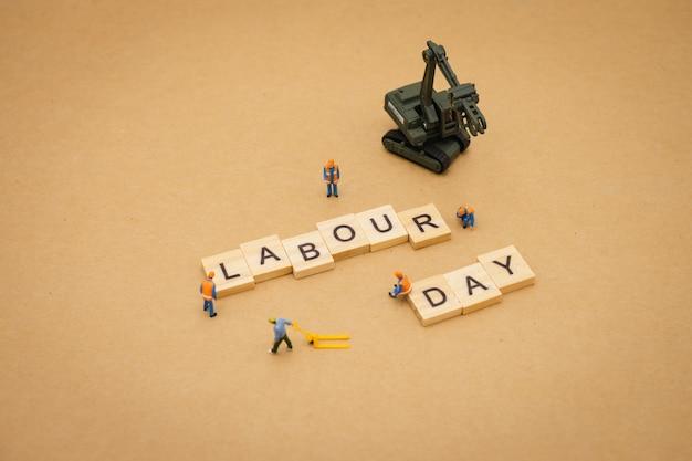 Miniatuur mensen die zich met de houten dag die van de woordarbeid bevinden als achtergrond universele dag gebruiken Premium Foto