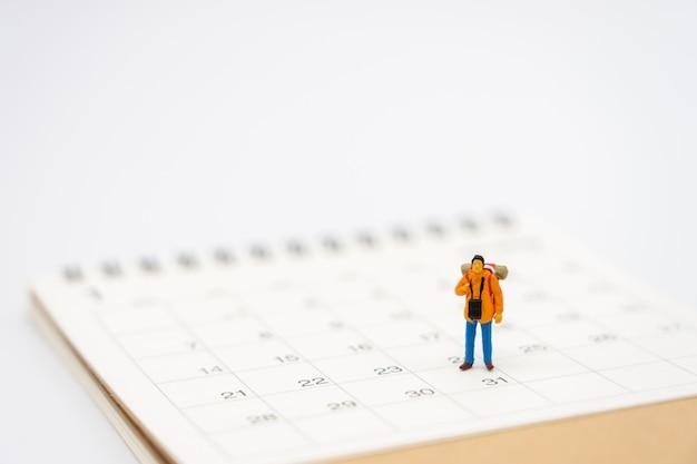 Miniatuur mensen staan op een boekenranglijst (lijst) het begin van de reis Premium Foto