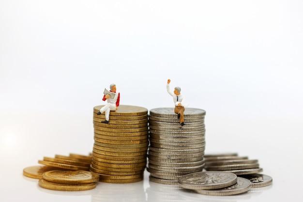 Miniatuur mensen: zakenman zittend op munten stapel. Premium Foto