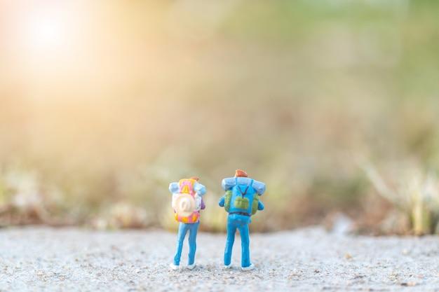Miniatuur mensenconcept met reizigersminiatuur met rugzak die zich op de weg bevinden Premium Foto