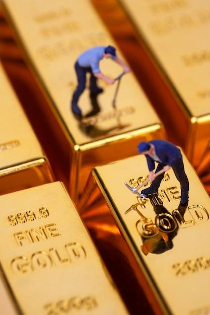 Miniatuur mijnwerker graaft op goudstaaf Premium Foto