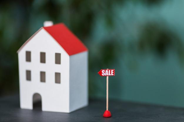 Miniatuur model van huis onroerend goed te koop tegen een wazige achtergrond Gratis Foto