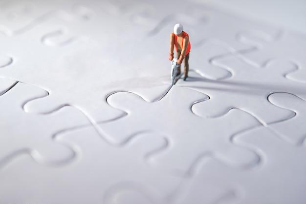 Miniatuur persoon bouwt puzzels, maakt plaats voor het team en werkconcept. inspanningsconcept Premium Foto