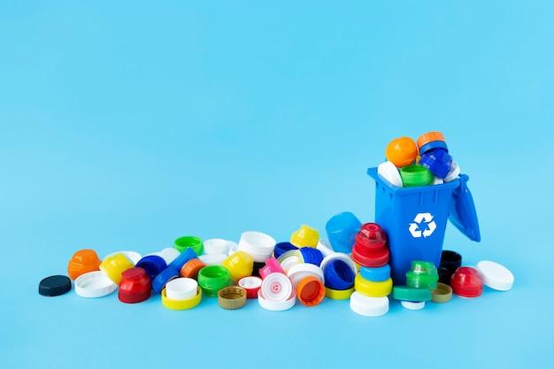 Miniatuur recycle container gevuld met plastic flessendoppen in verschillende maten, vormen en kleuren op lichtblauw. Premium Foto