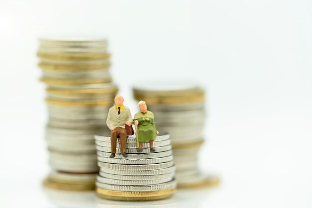 Miniatuur van gelukkige oude mensen die zich op muntstukkenstapel bevinden Premium Foto