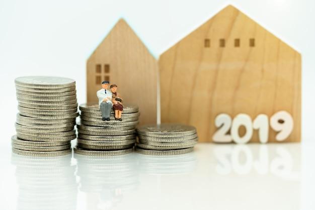 Miniatuur van oude mensen die op muntstukkenstapel zitten met huis Premium Foto