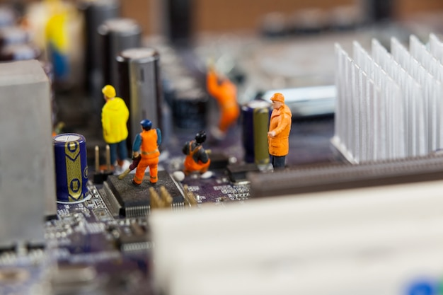 Miniatuur werknemers die op de chip van het moederbord Gratis Foto