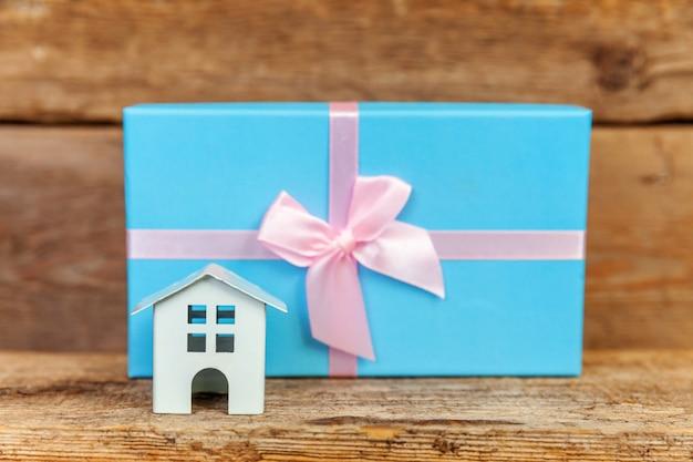 Miniatuur wit stuk speelgoed huis en giftdoos op houten achtergrond Premium Foto