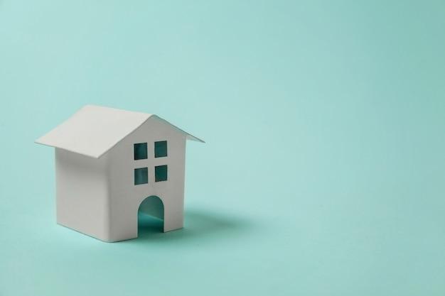 Miniatuur wit stuk speelgoed huis op blauwe achtergrond Premium Foto