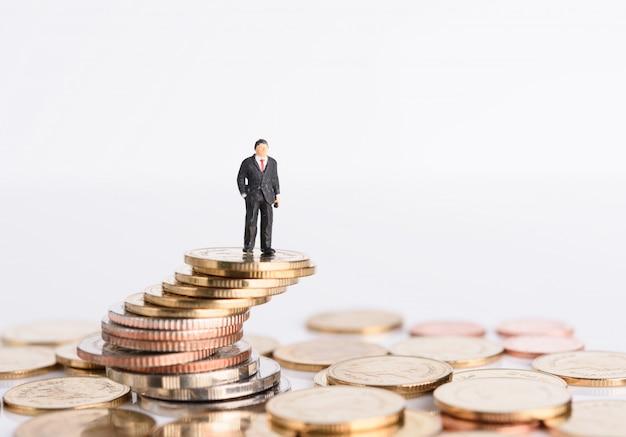 Miniatuur zakenmensen staan op geld munten geïsoleerd op wit, succesvol bedrijfsconcept Premium Foto
