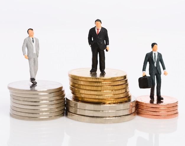 Miniatuur zakenmensen staan op geld munten geïsoleerd op wit, winnaar bedrijfsconcept Premium Foto