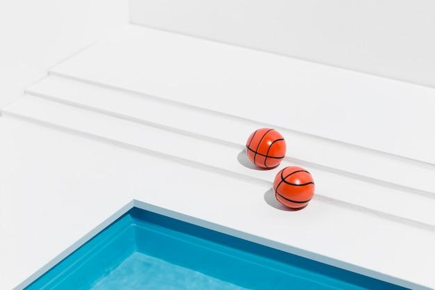 Miniatuur zwembad stilleven arrangement met basketballen Gratis Foto