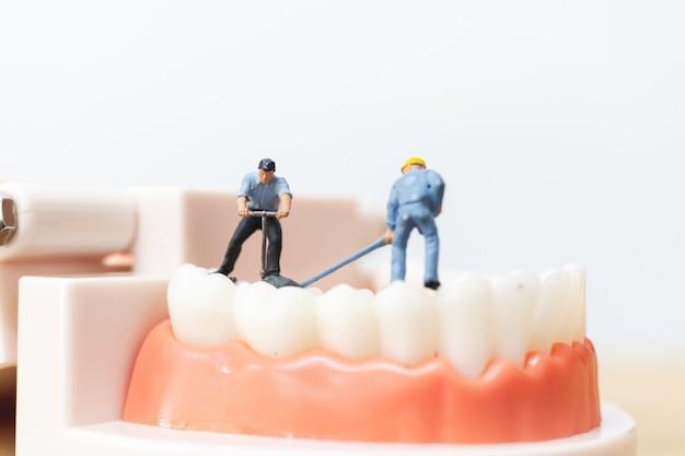 Miniatuurmensen: arbeidersteam dat een tand herstelt Premium Foto