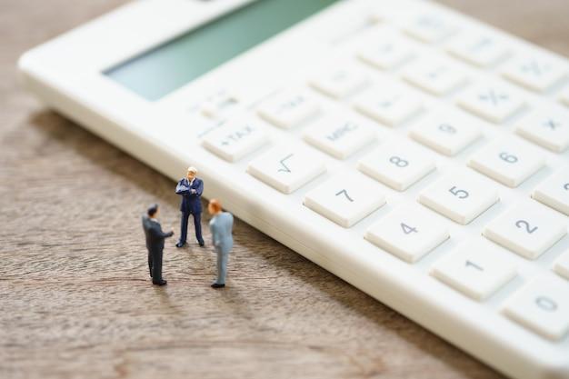 Miniatuurmensen betaalwachtrij jaarlijks inkomen (belasting) voor het jaar op rekenmachine. Premium Foto