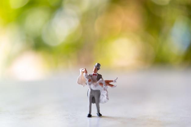 Miniatuurmensen: bruid en bruidegom in openlucht met groene bokehachtergrond en exemplaarruimte voor tekst Premium Foto