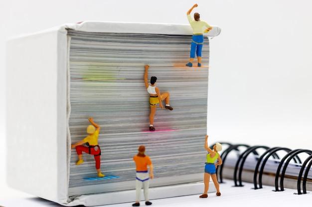 Miniatuurmensen die boek met uitdagende route op klip beklimmen. Premium Foto