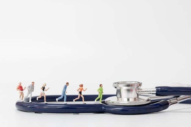 Miniatuurmensen die op stethoscoop lopen Premium Foto