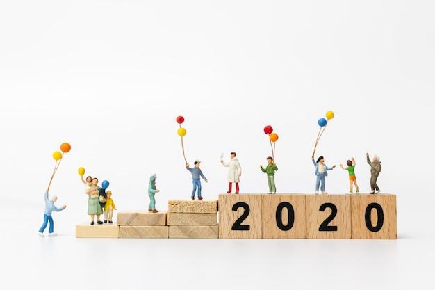 Miniatuurmensen: gelukkige familie houden ballon op houten blok nummer 2020 Premium Foto