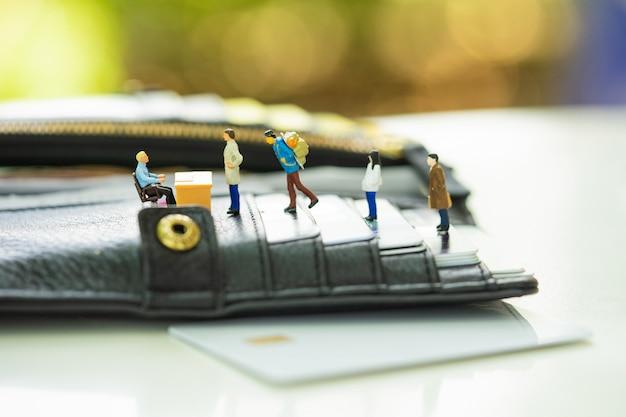 Miniatuurmensen in de rij bij de bankbalie op de portemonnee gevuld met creditcard. Premium Foto