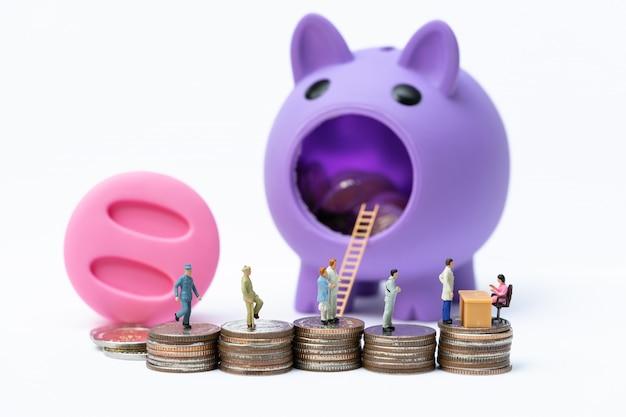 Miniatuurmensen in lijn bij de bankteller op de stapel muntstukken voor spaarvarken. Premium Foto
