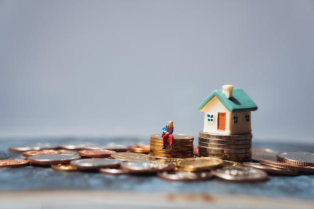 Miniatuurmensen, jonge vrouwenzitting op stapelmuntstukken Premium Foto