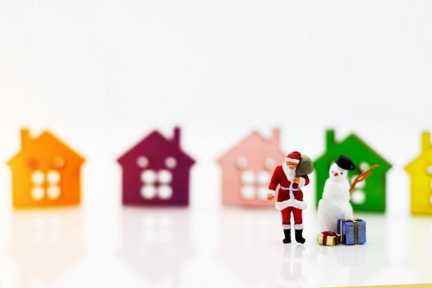 Miniatuurmensen: kerstman en sneeuwpop met cadeau staan voor houten huismodel. Premium Foto