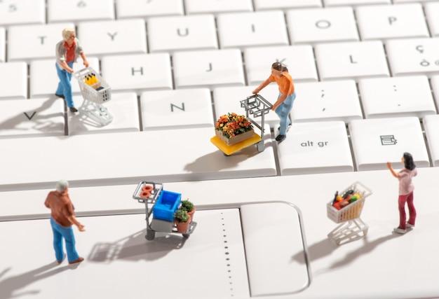 Miniatuurmensen met winkelwagentjes op een toetsenbord Premium Foto