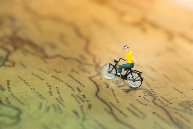 Miniatuurmensen: reizen met een rugzak op de fiets. Premium Foto