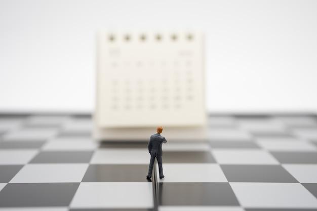 Miniatuurmensenzakenlieden die zich op witte kalender bevinden Premium Foto