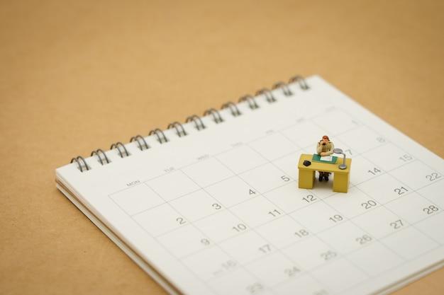 Miniatuurmensenzakenlieden op witte kalender die als achtergrond bedrijfsconcept gebruiken Premium Foto