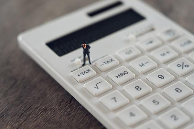 Miniatuurpersonen wachtrij jaarlijks inkomen (tax) voor het jaar op rekenmachine. Premium Foto