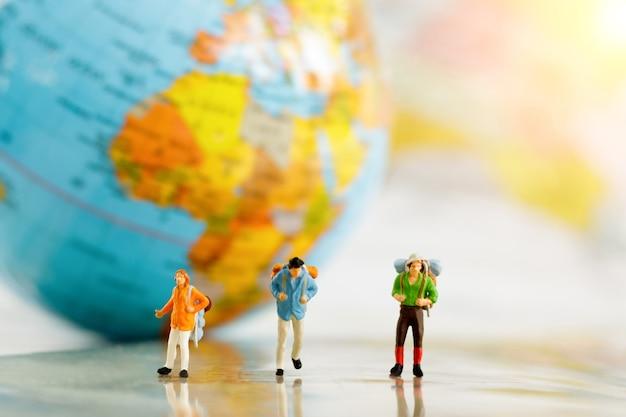 Miniatuurreizigers en rugzak op kaart en bol, concept reis rond de wereld en avontuur. Premium Foto