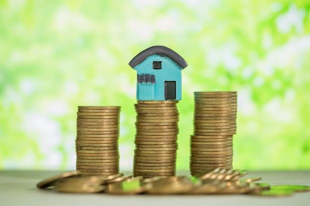 Minihuis op stapel muntstukken met groen onduidelijk beeld. Gratis Foto