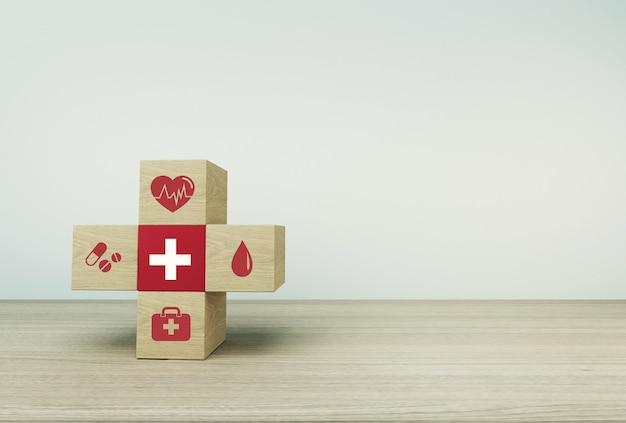 Minimaal conceptidee over van gezondheid en medische verzekering, die houtsnedestapelen schikken met pictogramgezondheidszorg medisch op lijstachtergrond. Premium Foto