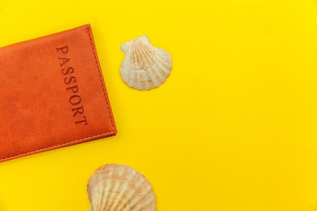 Minimale eenvoudige plat lag reis avontuur reisconcept met paspoort en shell op gele trendy moderne achtergrond Premium Foto