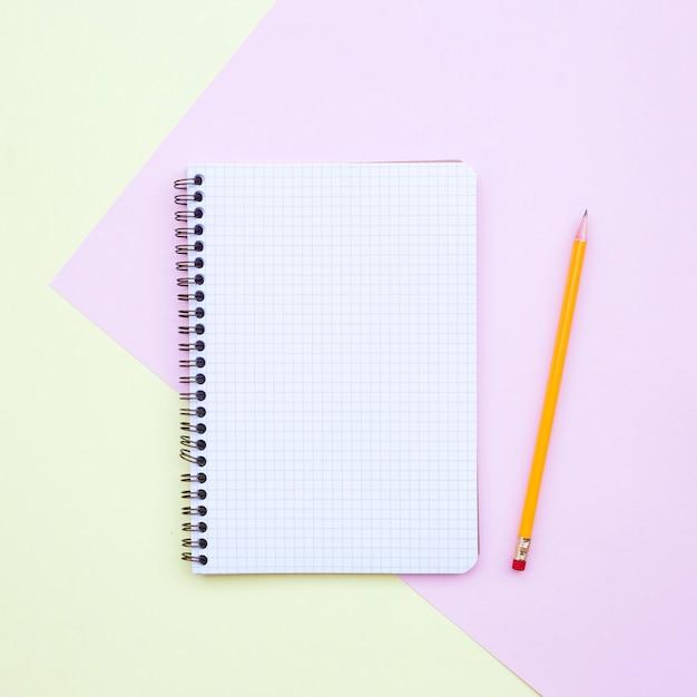 Minimale plat lag samenstelling met lege notebook met potlood op gele en roze achtergrond Gratis Foto