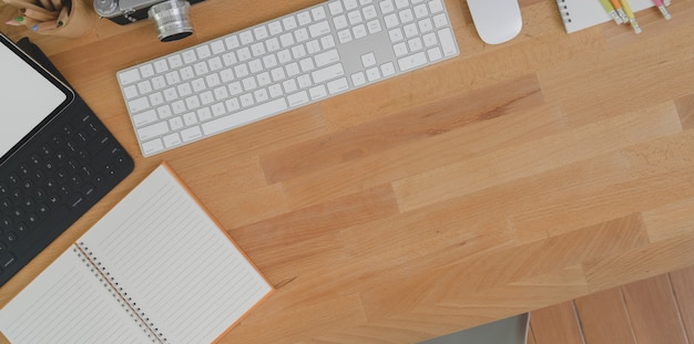 Minimale werkplek met tablet, lege notebook en kantoorbenodigdheden op houten tafel met kopie ruimte Premium Foto