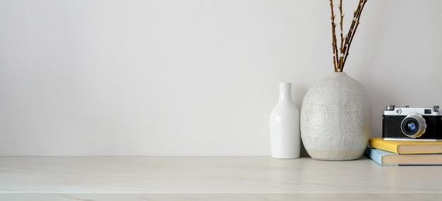 Minimale werkruimte met kopie ruimte, camera en kantoorbenodigdheden op wit bureau en witte muur Premium Foto