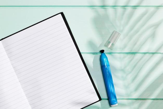 Minimalistisch notitieboekje met markeerstift en laat schaduw Gratis Foto