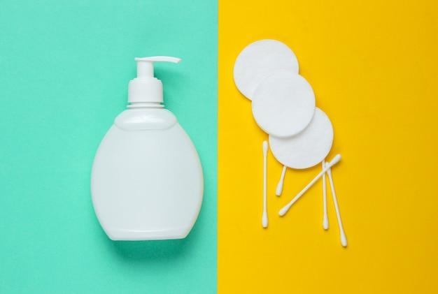 Minimalistisch schoonheidsconcept. flessenroom, wattenschijfjes, oorstokken op blauwgele achtergrond. Premium Foto