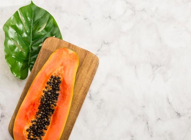 Minimalistische helft van papaja en monsterablad Gratis Foto