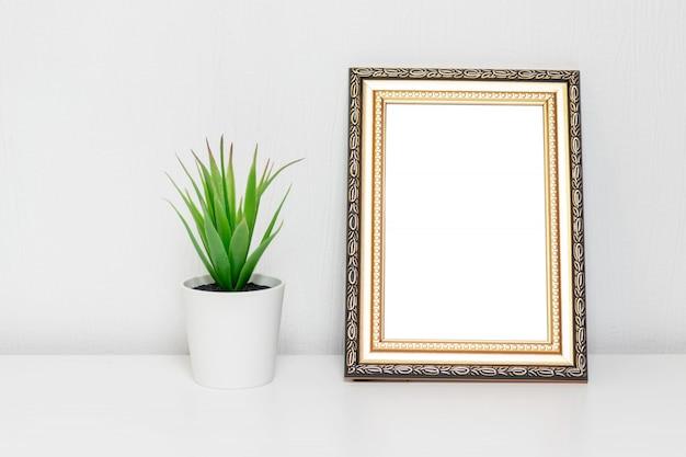 Minimalistische interieur met fotolijst en een plant in witte pot op een bureau Premium Foto